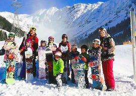 Kinder posieren für ein Gruppenfoto während dem Snowboardkurs für Kinder (5-12 Jahre) - Alle Levels mit ihrer freundlichen Lehrerin der Schule Out of Bounds Snowboard School.