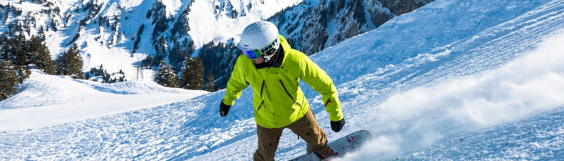 A snowboarder is going down a slope with confidence thanks to his Snowboarding Lessons (6-15 years) - 1 day with the swiss ski school Charmey.