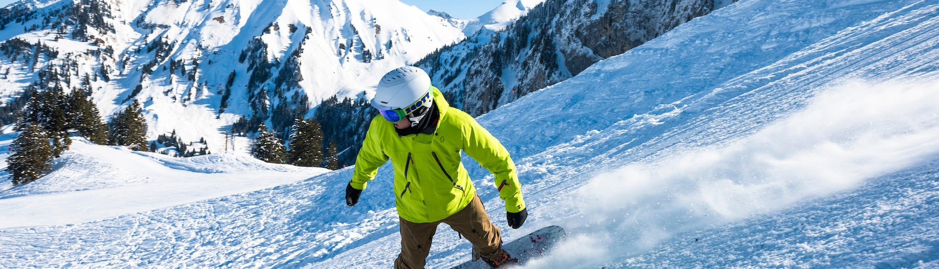 A snowboarder is going down a slope with confidence thanks to his Snowboarding Lessons (6-15 years) - 4 lessons - All Levels with the swiss ski school Charmey.