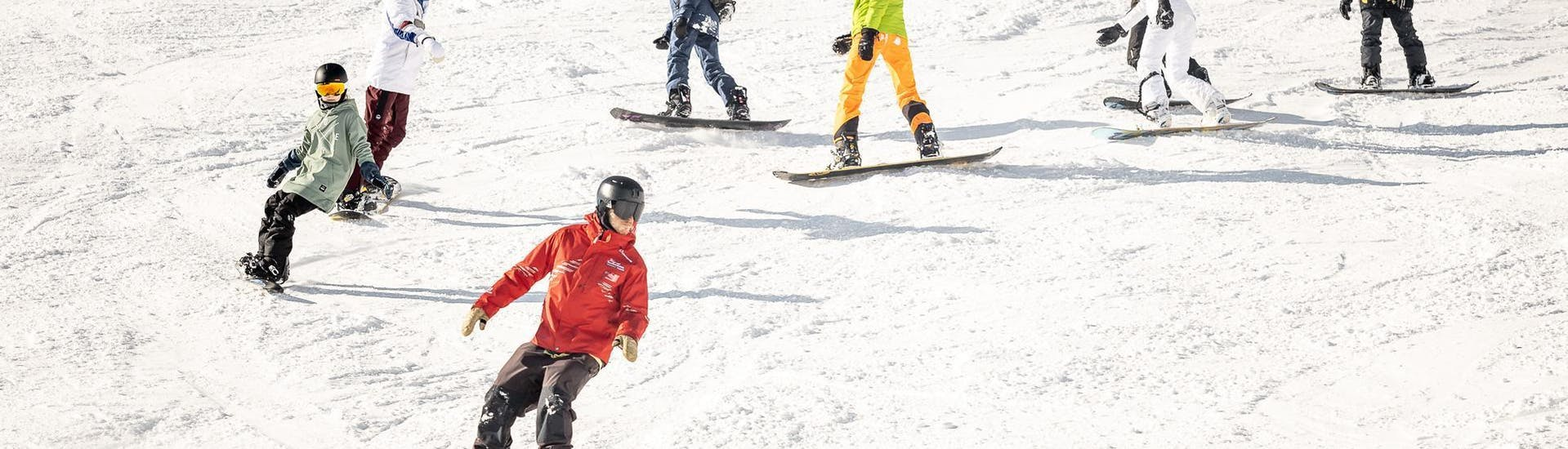 A group of  young snowboarders is learning how to master the board on the snowy slopes of the ski resort of Sölden during the Snowboarding Lessons for Kids (9-15 years) - All Levels organized by the ski school Ski & Snowboardschool Vacancia.