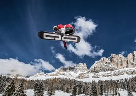 A snowboarder is doing a trick during Snowboarding Lessons for Kids & Adults - Advanced from the Carezza Skischool.