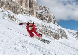 A snowboard instructor from Carezza Skischool is leading the way during Snowboarding Lessons for Kids & Adults - Beginner.
