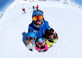 A ski instructor fro the ski school Prosneige Val Thorens & Les Menuires is teaching smiling kids during Snowboarding Lessons for Kids of All Ages and All Levels.