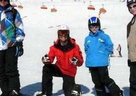 """Ein junger Snowboarder lächelt während der Aktivität Snowboardkurs für Kinder """"All-Inclusive"""" (9-15 Jahre) gemeinsam mit seinem Snowboardlehrer der Ski- und Snowboardschule Vacancia in die Kamera."""