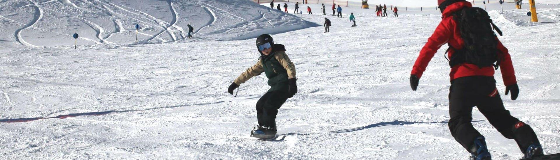 """Ein junger Snowboarder übt bei der Aktivität Snowboardkurs für Kinder """"All-Inclusive"""" (9-15 Jahre) mit der Ski- und Snowboardschule Vacancia seine Front- und Backside Turns."""