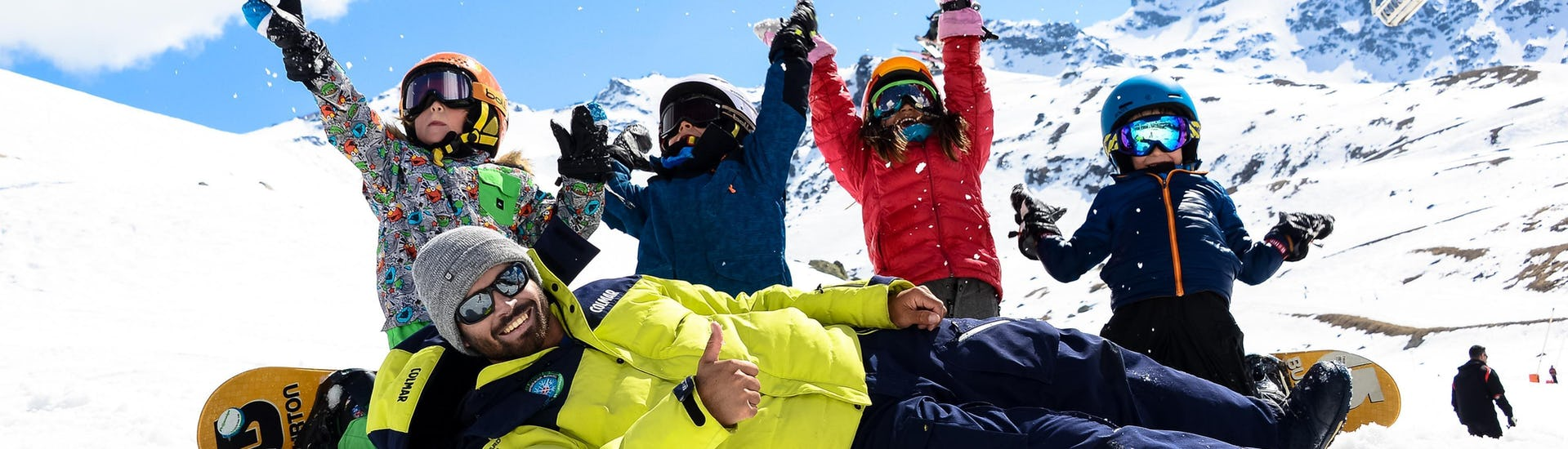Young snowboarders are throwing snow in the air behind their snowboard instructor from the ski school Prosneige Méribel during theirSnowboarding Lessons for Kids - All Levels & Ages.