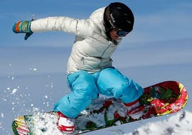 A snowboarder is doing a jump during their Snowboarding Lessons for Kids (8-12 years) - All Levels with the ski school ESF Alpe d'Huez.