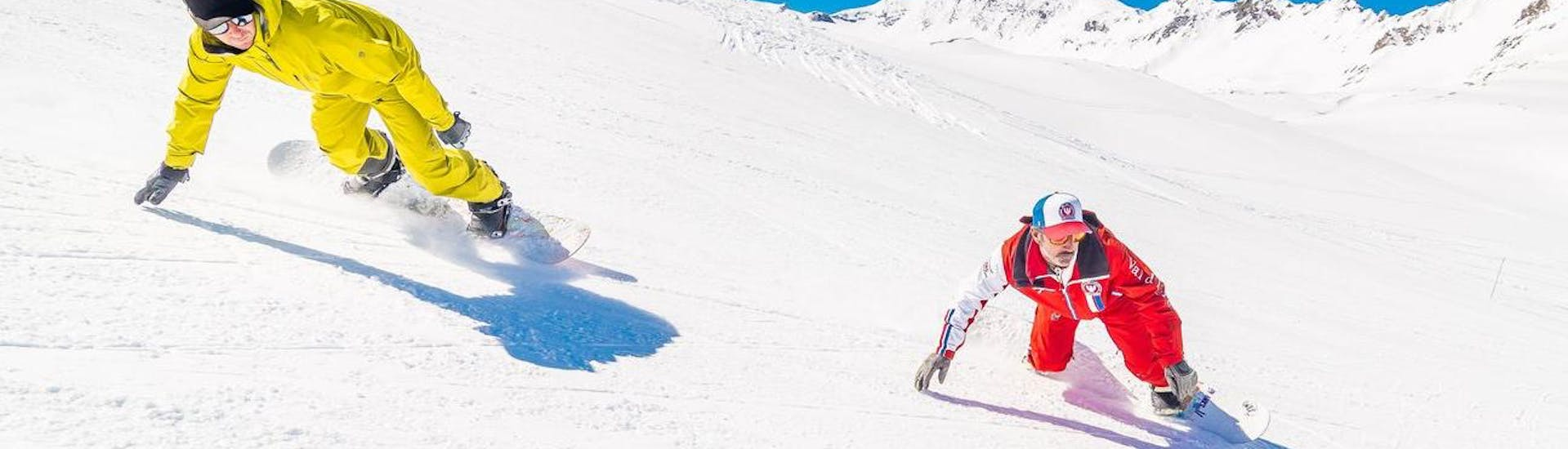 Two snowboarders are riding down the slope during the Snowboarding Lessons for Kids & Adults - All Levels organised by the school ESF Val d'Isère.