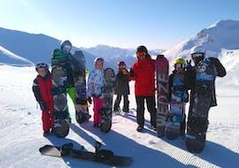 Des snowboardeurs et leur moniteur de snowboard de l'école de ski ESI Valfréjus prennent la pose pour une photo à la fin de leur Cours de snowboard pour Enfants & Adultes - Tous niveaux.