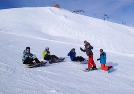 A group of snowboarders are sitting in the snow surrounding their snowboard instructor from the ski school Evolution 2  Tignes during theirSnowboarding Lessons for Kids & Adults - Afternoon.