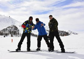 A group of friends enjoying their Snowboarding Lessons for Kids & Adults - All Levels organized by the ski school Scuola di Sci Olimpionica on the slopes of the Via Lattea ski resort in Sestriere.