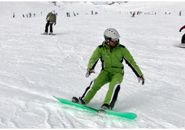 A snowboard instructor is mastering a slope in the ski area of Ötztal in Sölden during the Snowboarding Lessons for Kids & Adults - All Levels organized by the ski school Ski- and Bike School Ötztal Sölden.