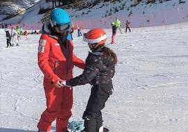 A snowboard instructor is teaching the basics of snowboarding to a young participant of the Snowboarding Lessons for Kids & Adults - First Timer organized by the ski school Scuola di Sci Val Rendena in the ski resort of Pinzolo.