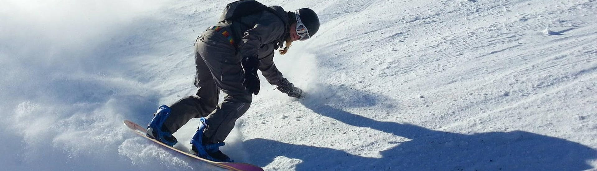 A female snowboarder is drawing tracks in the freshly prepared ski piste during her snowboarding lessons for kids and adults with Skischule Schwarzenberg am Bödele.