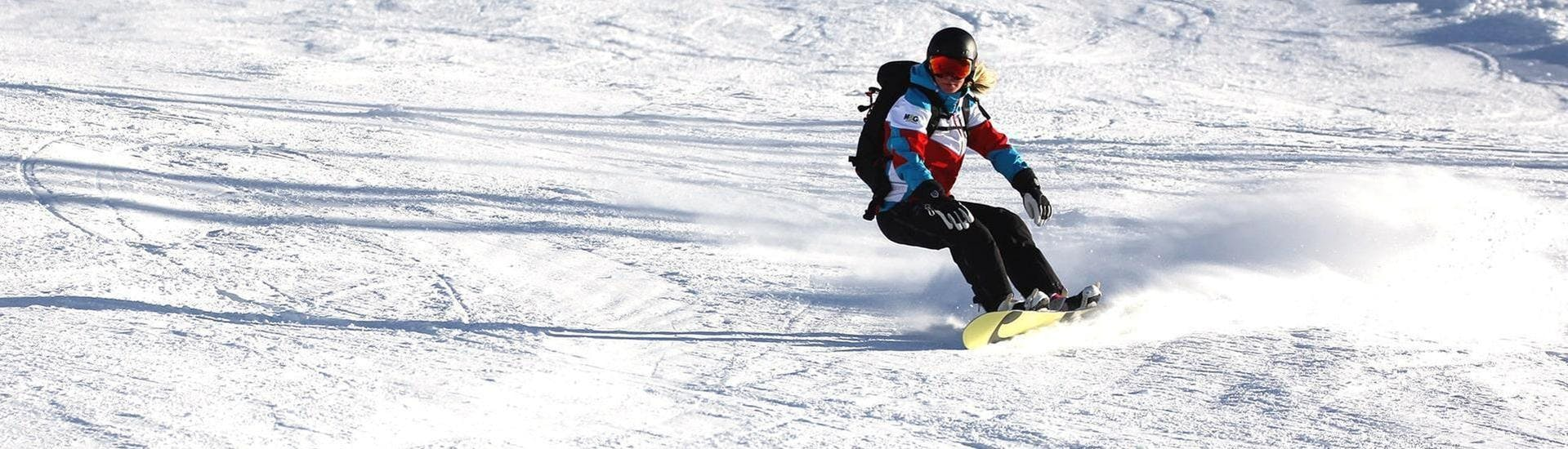A female snowboarder is snowboarding down a sunny slope during one of her Snowboarding Lessons for Kids & Adults - Full Day - Advanced in the sski resort of Ischgl.