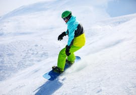 A snowboarder is mastering a slope in Sestriere during a Snowboarding Lessons for Kids & Adults - Holidays offered by the school Scuola di Sci Olimpionica.