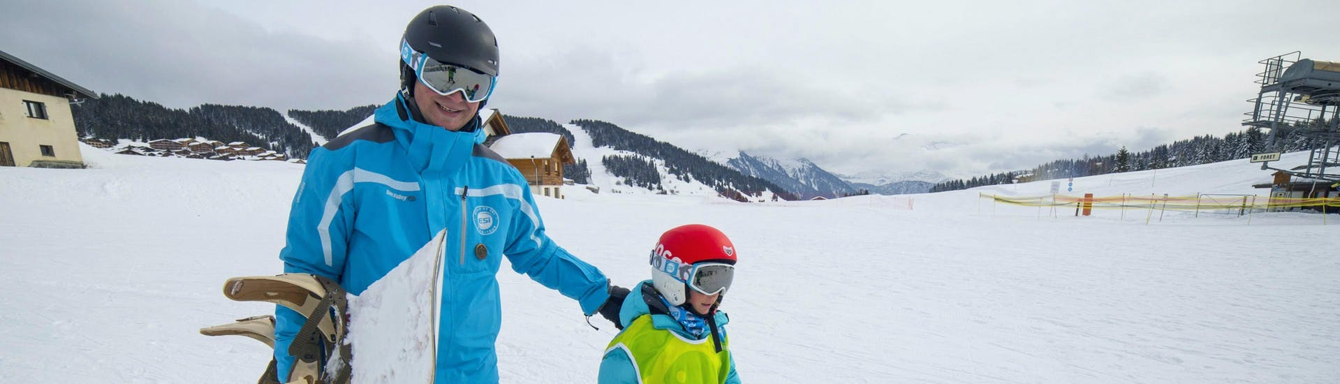 A snowboarder is walking besides their snowboard instructor from the ski school ESI Font Romeu at the bottom of the snowy slopes during their  Snowboarding Lessons for Kids & Adults - Low Season.