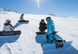Snowboarders are sitting in the snow and listening to the instructions of their snowboard instructor from the ski school ESI Dévoluy before starting their Snowboarding Lessons for Kids (from 7 years).