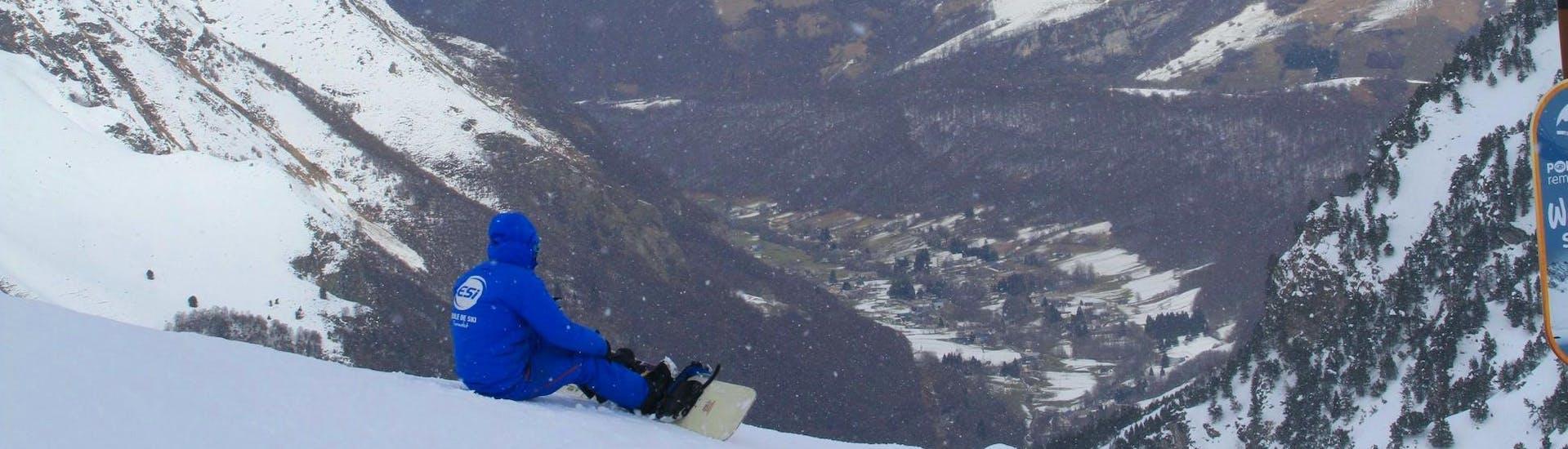 Un snowboarder está sentado en la nieve contemplando el valle de abajo durante sus clases de snowboard para niños (a partir de los 8 años) con la escuela de esquí ESI du Tourmalet en La Mongie.