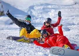 Two snowboarders are sitting in the snow surrounding their snowboard instructor from the ski school ESF Alpe d'Huez during their Snowboarding Lessons for Teens & Adults - All Levels.