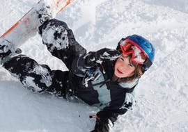 A young snowboarder is sitting in the snow during his Snowboarding Lessons (from 8 years) - All Levels with the ski school Moonshot La Bresse.