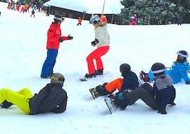 Pendant son Cours de snowboard pour Enfants (9-14 ans) - Tous niveaux avec l'école de ski Schneesportschule Thoma, un moniteur de snowboard explique les bases du snowboard à un groupe d'enfants.