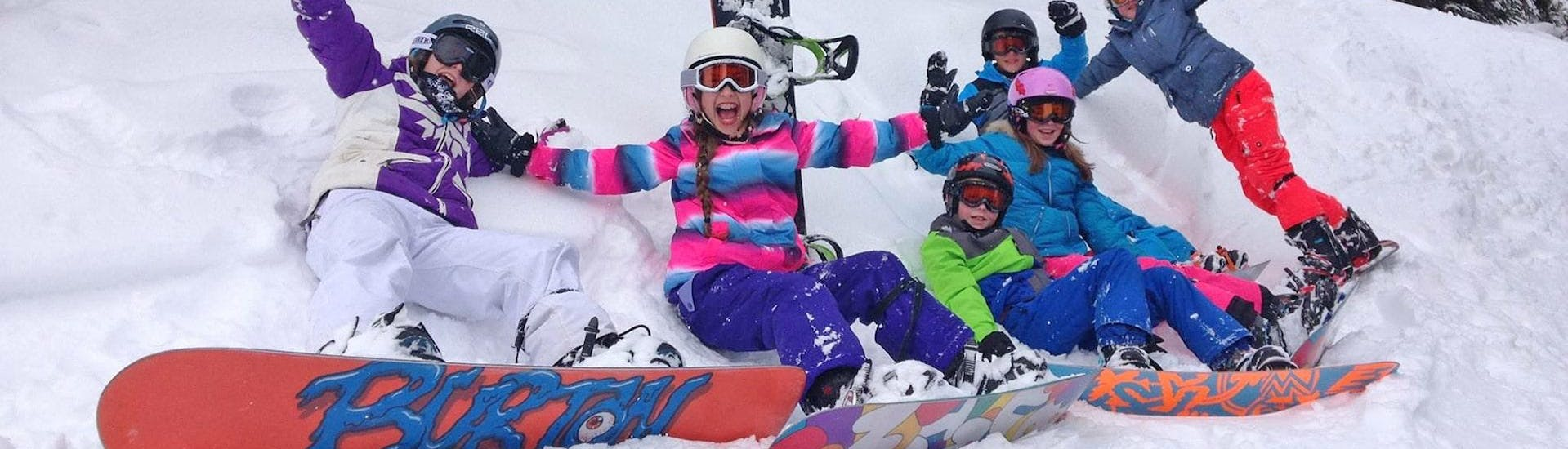 "A group of children enjoying themselves during their Snowboarding Lessons ""Young Boarder Zone"" (7-14 years) with BOARD.AT."