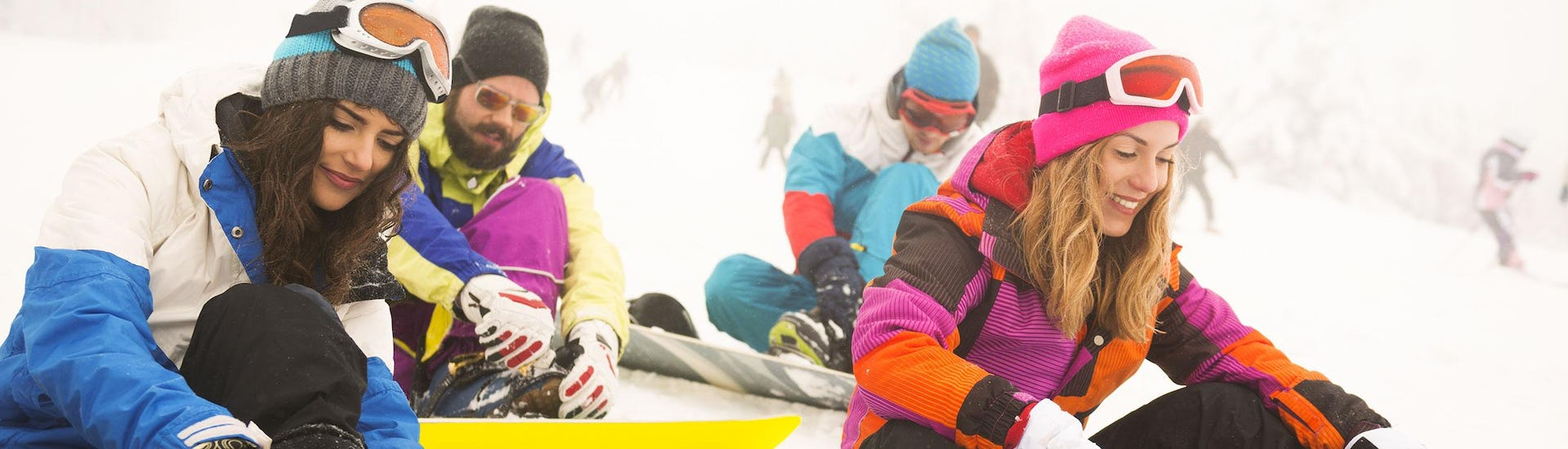 A group of snowboarders strapping on their snowboards during one of the Snowboard Instructor Private - All Levels & Ages organised by Escuela de Esquí Slalom.