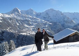 A couple is enjoying the beautiful winter wonderland on a snowshoeing tour with Outdoor Interlaken.