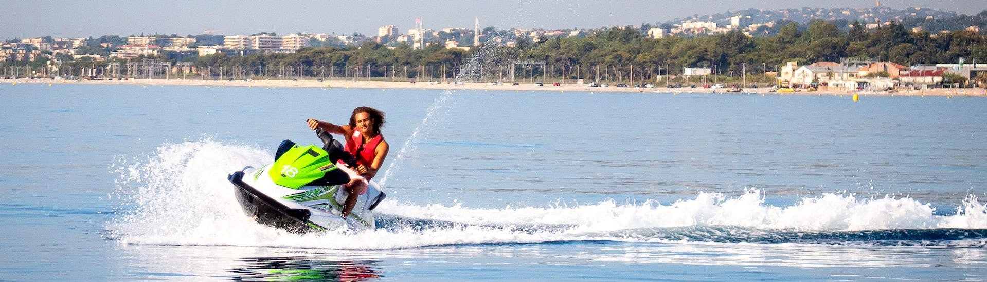 A man is having fun while jet skiing during his tour with Jet Ski Hire in Cagnes-sur-Mer with Plage des Marines.