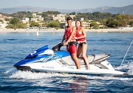 A young couple is standing in their jet ski in front of a beautiful landscape of the French Riviera during their tour with Jet Ski Hire in Cagnes-sur-Mer with Plages des Marines.