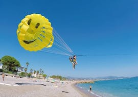 Friends are taking off from the beach while starting Parasailing in Villeneuve-Loubet with Plage des Marines.