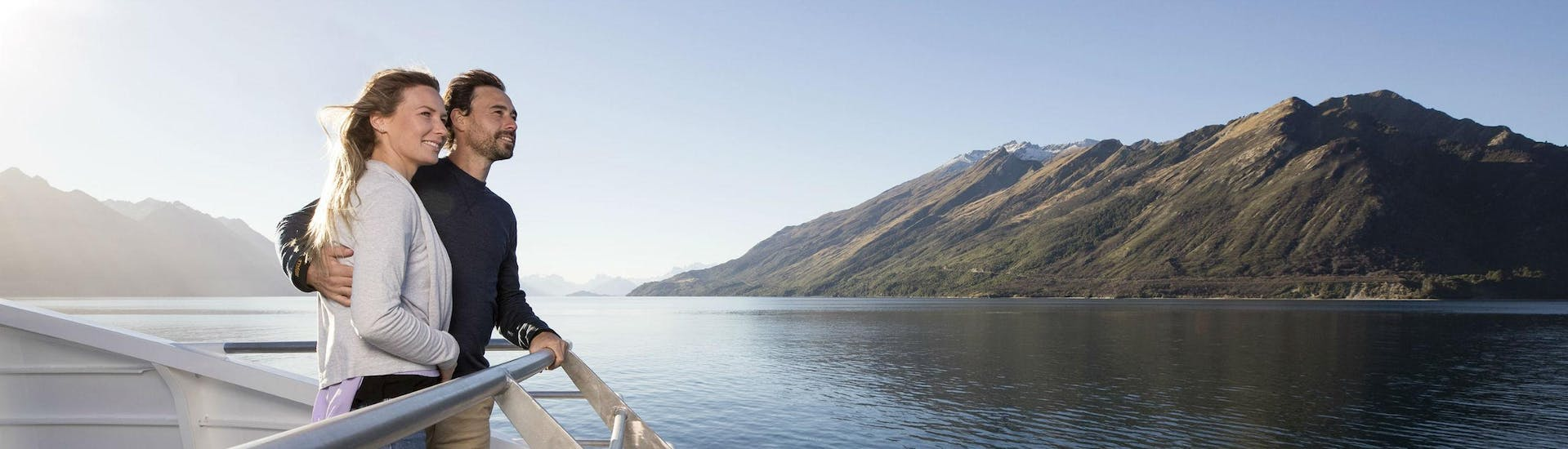 A couple is enjoying the view from the catamaran's viewing deck during the Spirit of Queenstown Cruise on Lake Wakatipu organised by Southern Discoveries.