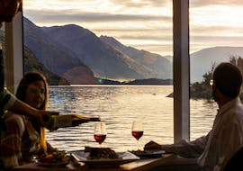 A couple is enjoying a glass of red wine during the Spirit of Queenstown Dinner Cruise organised by Southern Discoveries.