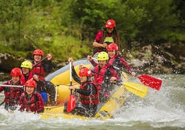 A group of people riding the waves of Salzach River on their sportive rafting tour with Torrent Outdoor Experience.