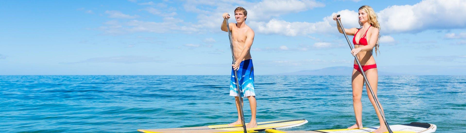 Un couple fait du stand up paddle dans la destination de vacances Puerto del Carmen.