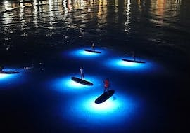 The tour participants enjoy paddling on the LED-lit SUP boards during their Stand Up Paddling Tour by Night from Granadella Beach with Siesta Advisor Jávea.