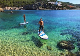 A man paddles relaxed through the crystal clear waters and enjoys the view during the Stand Up Paddling Tour to Bays and Caves in Ibiza with Mediterrania Paddle Surf Ibiza.
