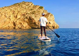 A girl paddles towards the rock to watch it up close during her Stand Up Paddling Tour to Blue Lagoon and Caves with Siesta Advisor Jávea.