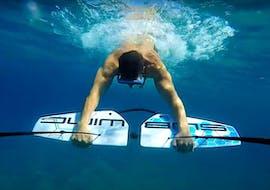 Un ragazzo si aggrappa al subwing sott'acqua trasportato dalla barca durante il Subwing a Ramla Bay con Vitamin Sea.