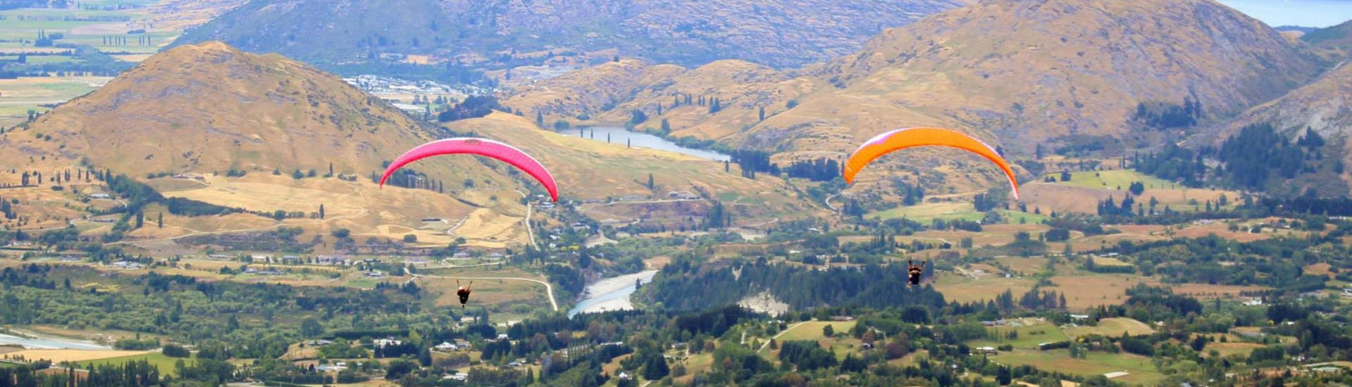 Two paragliders from Skytrek Queenstown are flying next to each other while Paragliding in Queenstown - Summer.