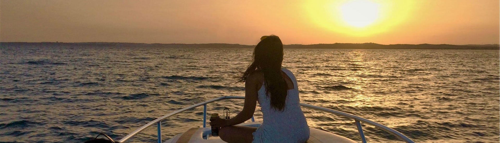 A young woman is looking out towards the horizon during the Sunset Boat Tour - Benagil with Seasiren Tours.
