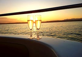 Two glasses of wine with breathtaking sunset in the background on Sirmione Boats motorboat during a sunset boat trip along the Sirmione peninsula.