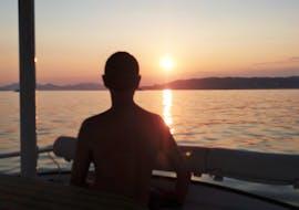 Un homme regarde le coucher de soleil lors d'une balade privée en catamaran dans la baie de Juan-les-Pins avec SeaZen.