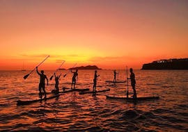 The tour participants paddle during a beautiful sunset at the sea during their Sunset Stand Up Paddling Tour in Ibiza with Mediterrania Paddle Surf Ibiza.