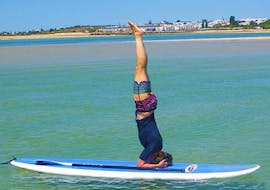 During the Sunset SUP Yoga at Praia da Fuseta with Kite Culture Algarve, a participant is practicing a headstand on the SUP board.