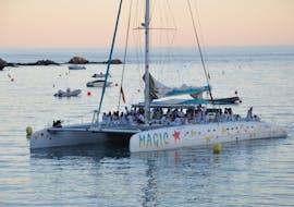 Un bateau de Magic Catamarans navigue autour de la baie de Roses alors que le soleil se couche dans cette Sortie en catamaran au coucher du soleil depuis Roses.