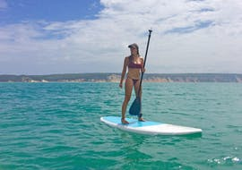 A young woman is standing on a stand up paddle board at Double Island Point during the SUP Noosa wildlife day trip with Epic Ocean Adventures Noosa.