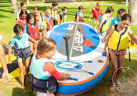 A group of children are carrying the SUP board they received with their Stand Up Paddleboarding Rental in Jàvea with Anywhere Watersports.