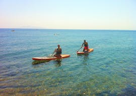 Two friends are exploring the Santorini coastline during the SUP Rental at Kamari Beach in Santorini with Kamari Beach Watersports Santorini.